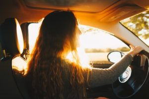 woman with long hair driving a car with the sunlight coming in behind her.
