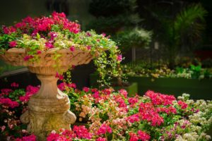 A large ceramic fountain filled with overflowing pink flowers.