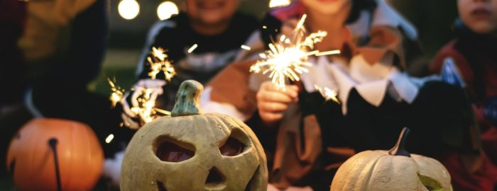 Kids holding sparklers while carving jackolanterns.