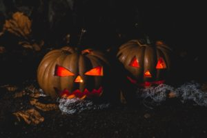 Spooky looking jackolanterns lit up with candles.
