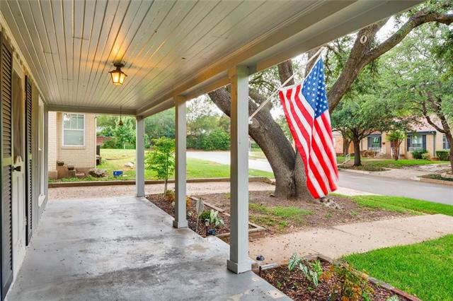 Side shot of the spacious front porch with an American flag hanging from the front.