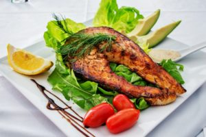 Grilled fish on a bed of lettuce.