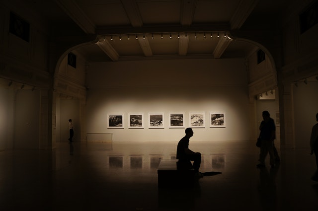 A person sitting and looking at art in a gallery