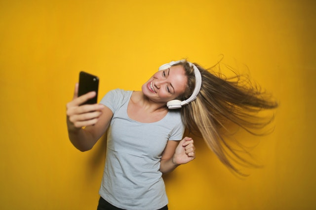 A woman taking a selfie in front of a yellow wall