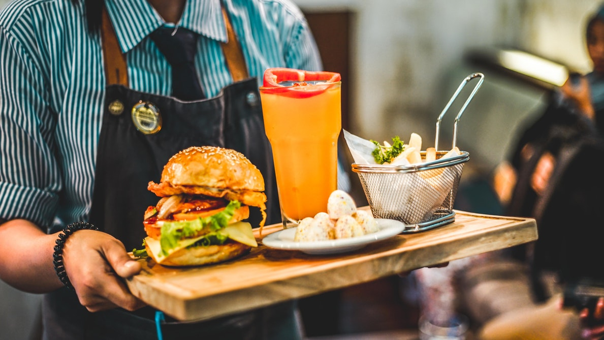 A person carrying a tray with a burger, fries, and a drink.