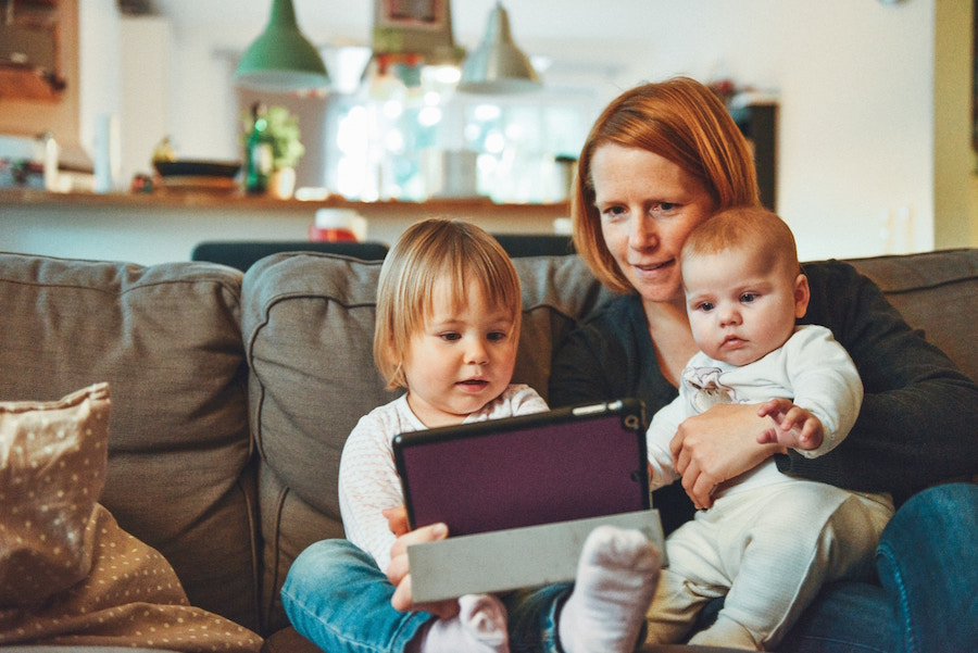 Woman and two children using a tablet on a couch.