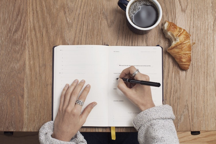 A person writing in a journal, eating a croissant, and drinking a cup of coffee.
