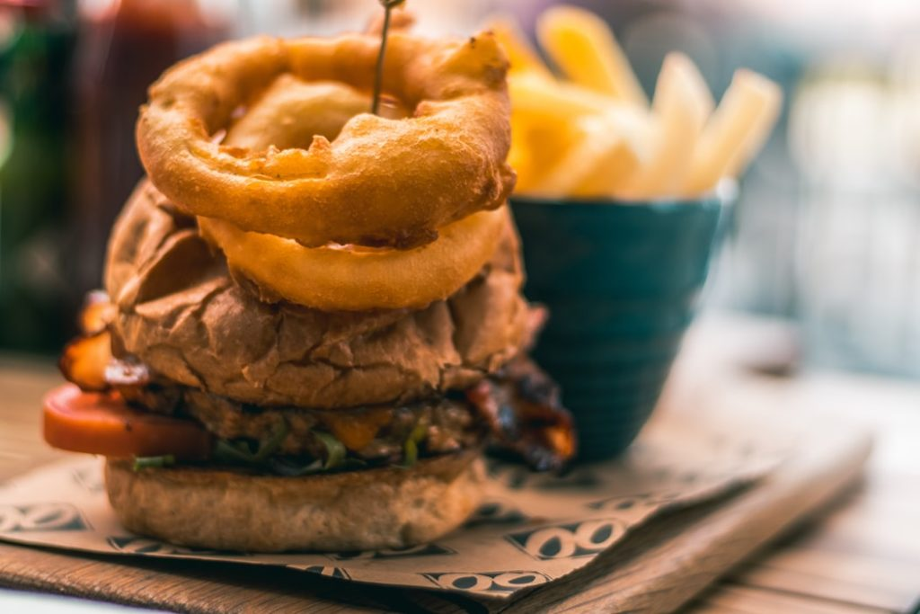 A burger topped with onion rings and a side of fries.