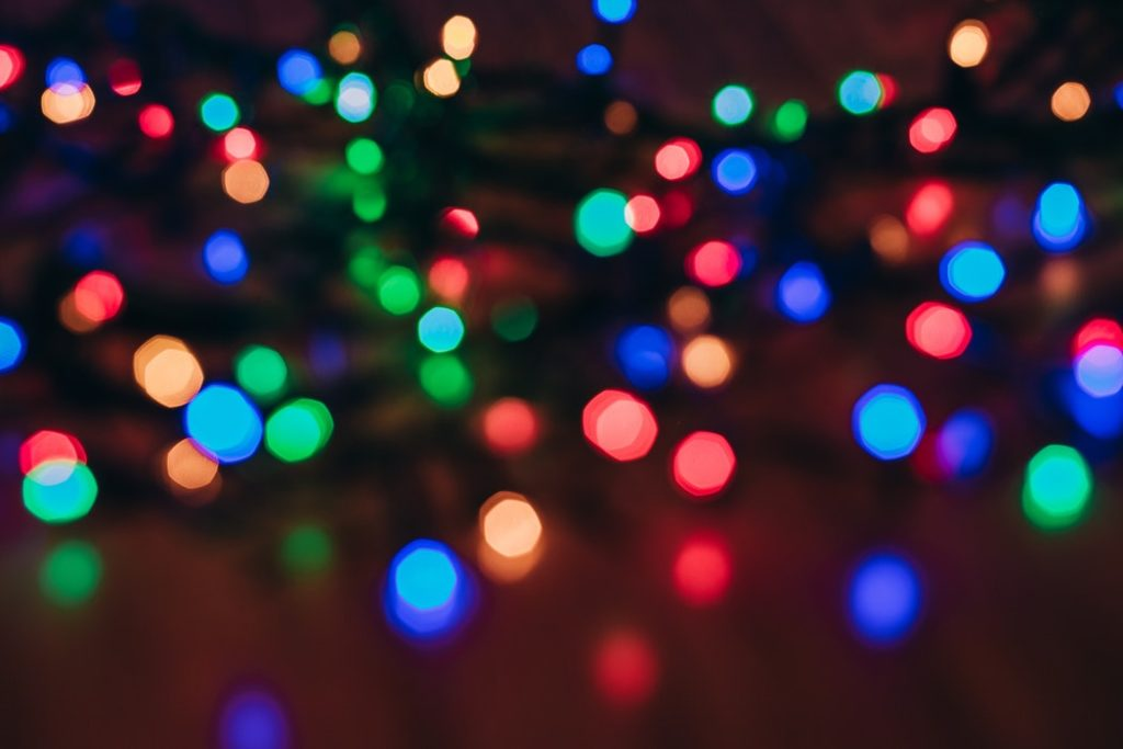 Multicolored holiday lights out of focus.