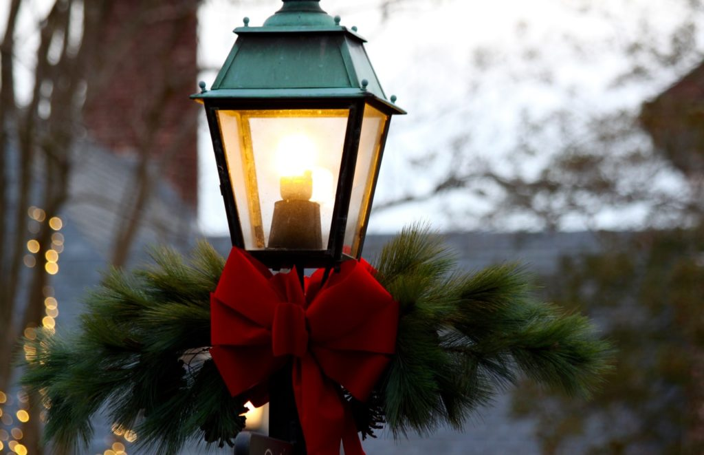 A red bow on a street light surrounded by greenery and for a home staging.
