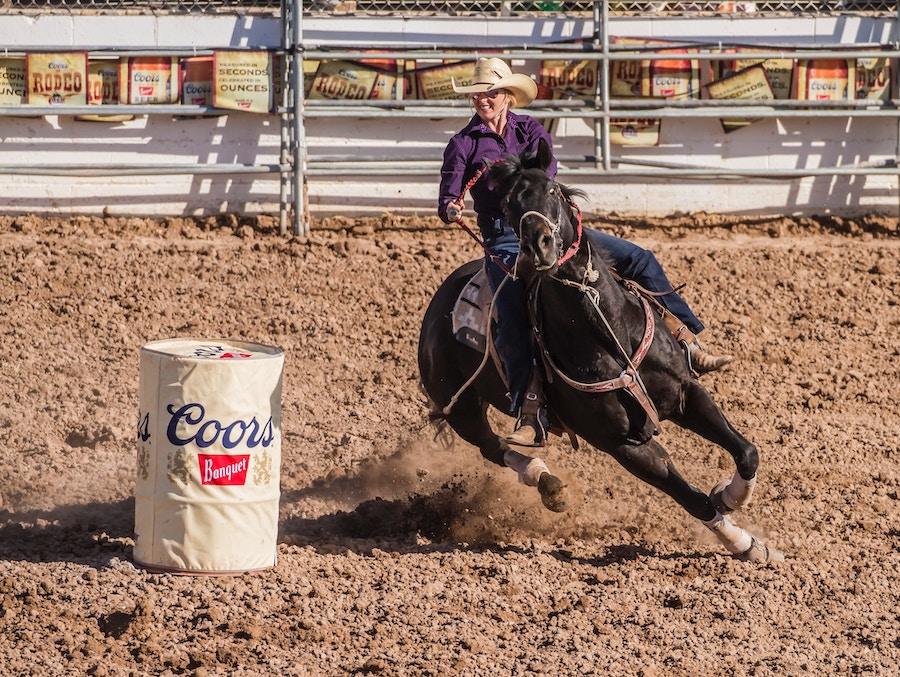Woman barrel racing on a horse